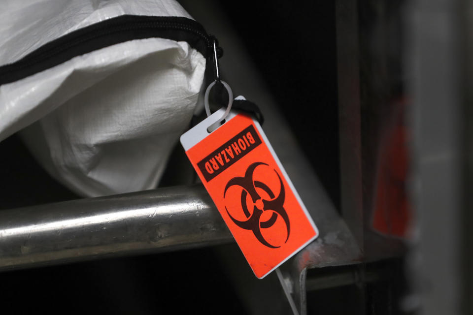 In this Tuesday, May 5, 2020, photo, an orange biohazard tag hangs from a body bag in an isolated refrigerated unit set aside for bodies infected with coronavirus at the Cook County morgue in Chicago. (AP Photo/Charles Rex Arbogast)