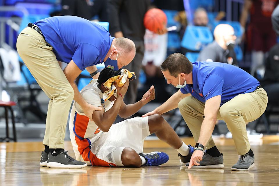INDIANAPOLIS, INDIANA - MARCH 19: Tyree Appleby #22 of the Florida Gators sits injured on the ground as he is tended to by head coach Mike White (R) of the Florida Gators in the second half against the Virginia Tech Hokies in the first round game of the 2021 NCAA Men's Basketball Tournament at Hinkle Fieldhouse on March 19, 2021 in Indianapolis, Indiana. (Photo by Andy Lyons/Getty Images)