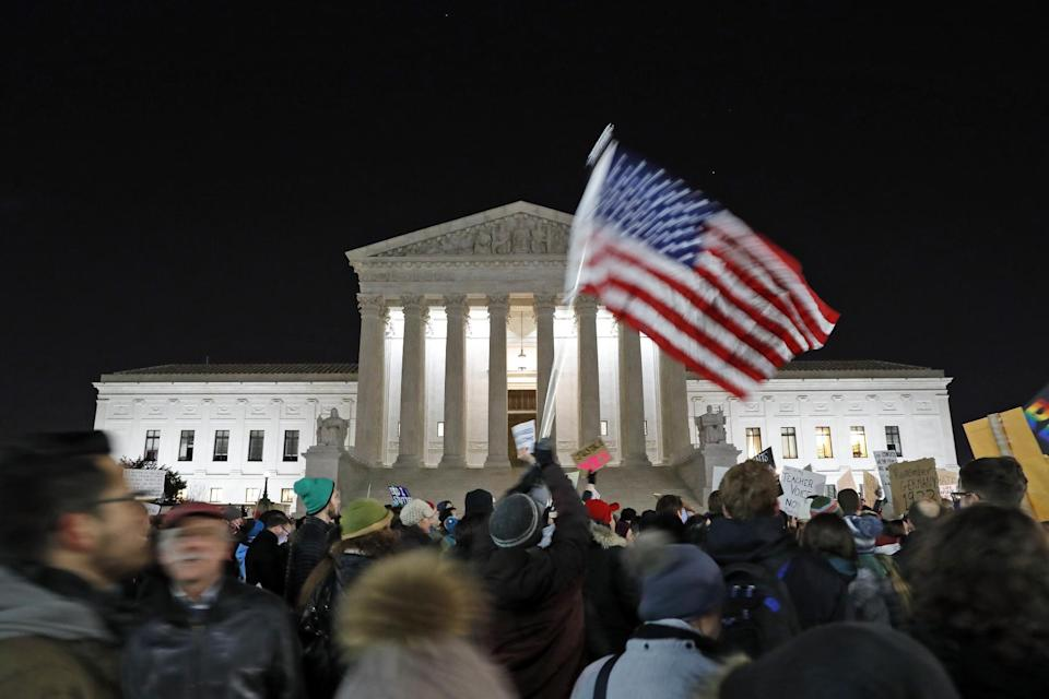 In this Jan. 30, 2017, photo, a protester waves an American flag in front of the Supreme Court during a protest about President Donald Trump's recent executive orders in Washington. Two weeks into his presidency, Donald Trump has thrown Washington into a state of anxious uncertainty. Policy pronouncements sprout up from the White House in rapid succession. Some have far-reaching implications, most notably Trump's temporary refugee and immigration ban, but others disappear without explanation, including planned executive actions on cybersecurity and the president's demand for an investigation into unsubstantiated voter fraud. The day's agenda can quickly be overtaken by presidential tweets, which often start flashing on smartphones just as the nation's capital is waking up. (AP Photo/Alex Brandon)