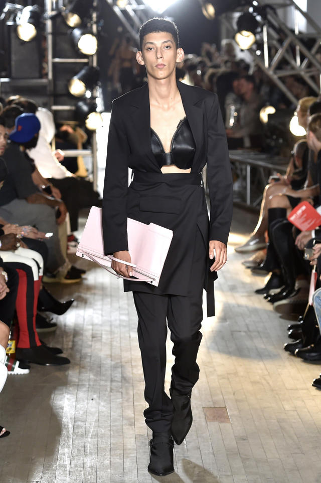 In case you need more storage than your bra bag can provide, this model is also carrying a clutch. (Catwalking via Getty Images)