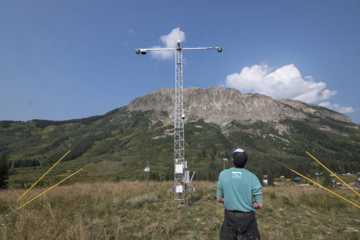 In this Aug. 16, 2021 photo provided Lawrence Berkeley National Laboratory, John Bilberry looks up at an Atmospheric Radiation Measurement instrument tower installed for the Surface Atmosphere Integrated Field Laboratory (SAIL) field campaign in Gothic, Colo. The SAIL campaign will provide insights into mountainous water-cycle processes. Federal scientists are launching an effort to better understand the hydrology in the U.S. West. The U.S. Department of Energy on Tuesday, Aug. 24 announced a new kind of climate observatory near the headwaters of the Colorado River. (David Chu/Lawrence Berkeley National Laboratory via AP)