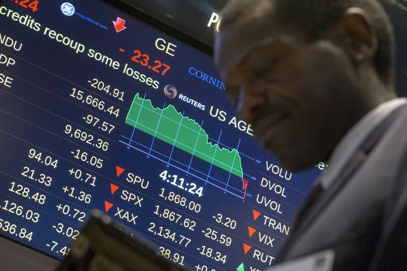 A screen displays the Dow Jones Industrial Average as a trader passes by on the floor after the closing bell at the New York Stock Exchange