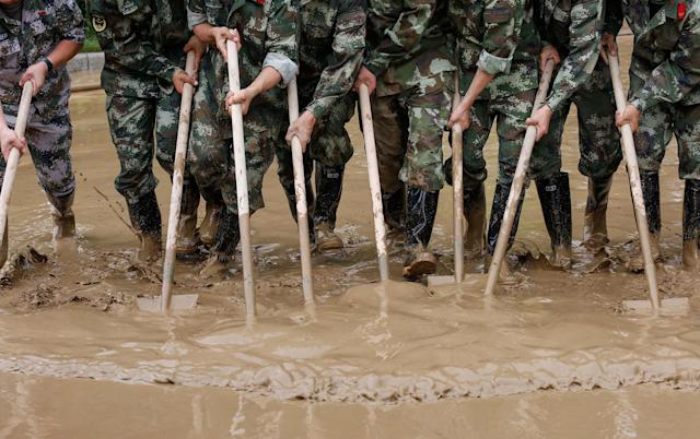 <p>Paramilitary policemen sweep a flooded street in Guilin, Guangxi province, China, July 3, 2017. (Photo: Stringer/Reuters) </p>