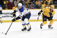 St. Louis Blues defenseman Carl Gunnarsson (4), of Sweden, passes the puck in front of Nashville Predators left wing Daniel Carr (26) during the second period of an NHL hockey game Monday, Nov. 25, 2019, in Nashville, Tenn. (AP Photo/Mark Zaleski)
