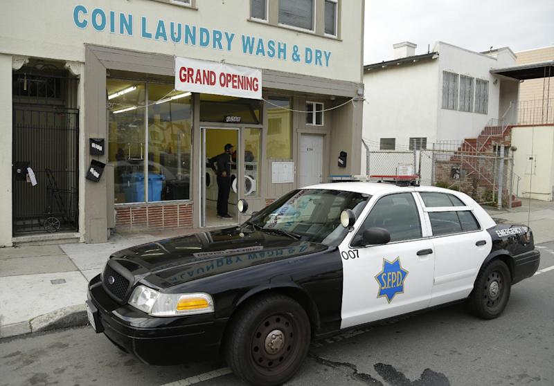 "A San Francisco police car is parked in front of a laundromat where an argument started, which resulted in a woman being set on fire Sunday, Jan. 6, 2013, in San Francisco. San Francisco police say a woman is hospitalized with what are being described as ""life-threatening injuries"" after someone poured a flammable liquid on her and set her on fire. (AP Photo/Ben Margot)"