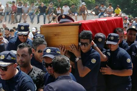 Police officers carry the coffin of their comrade during his funeral in Sidi Hassine