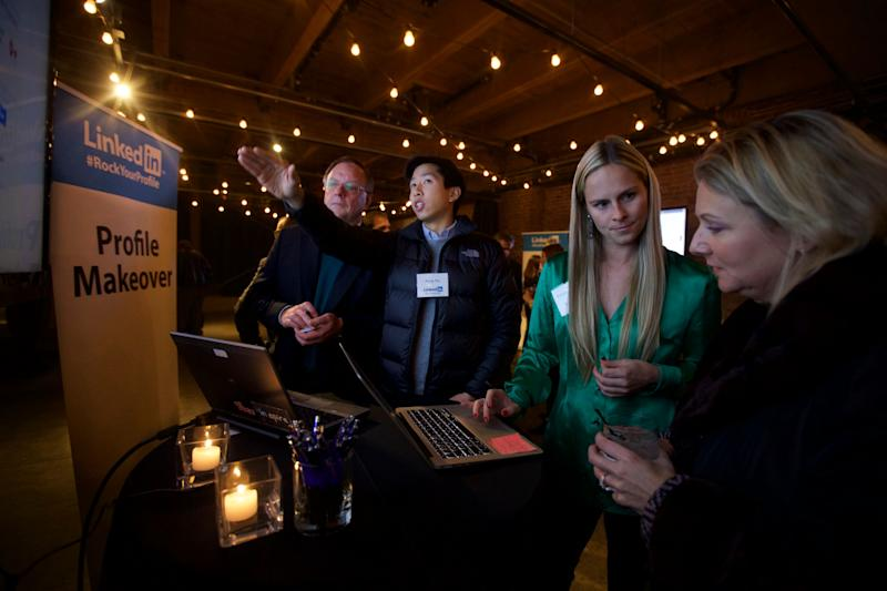 IMAGE DISTRIBUTED FOR LINKEDIN - LinkedIn coaches Andy Ku, second from left, and Krista Canfield, second from right, help Harry Wilson, far left, of Maple Valley, Wash., and Dana Russell of Snoqualmie, Wash., with their LinkedIn profiles during one of several LinkedIn #RockYourProfile events on Thursday, Nov. 13, 2014 in Seattle. (Stephen Brashear/AP Images for LinkedIn)