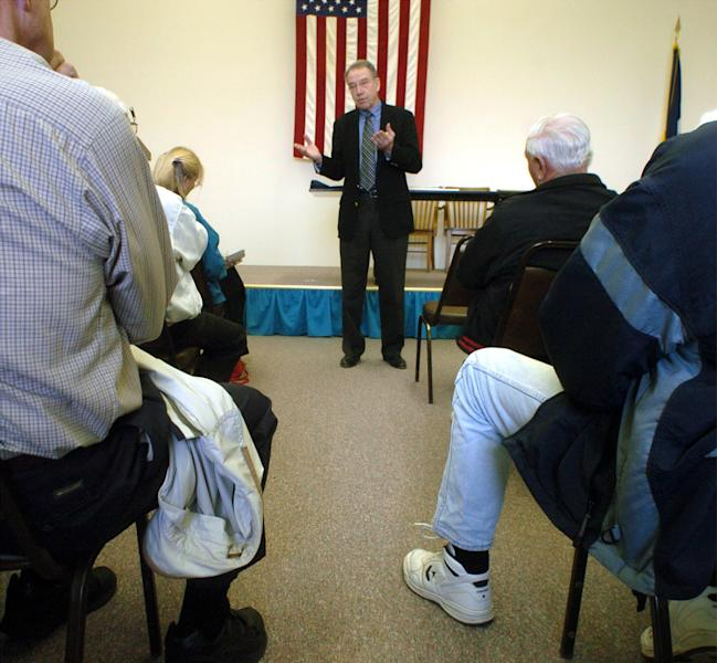 FILE – In this March 23, 2005 file photo Sen. Charles Grassley, R-Iowa, talks to constituents during a town hall meeting in Clarinda, Iowa. During a recent town hall meeting farmers, nurses and veterans all took turns pressing Grassley on gun control, immigration, the deficit and the IRS scandal, and listening to the Republican's answers. Some applauded. Others scoffed. But all embraced the chance to put their representative to Washington on the spot, face-to-face during a staple of American civics that's growing increasingly scarce _ the town-hall style meeting. (AP Photo/Dave Weaver, File)