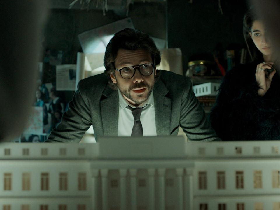 """A still from """"Money Heist,"""" in which The Professor speaks in front of a model of a building."""
