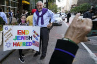 """A young girl poses for a cell phone photo with a homemade sign as she joined protesters outside the offices of New York Gov. Andrew Cuomo, Thursday, Oct. 15, 2020, in New York. Three Rockland County Jewish congregations are suing New York state and Gov. Andrew Cuomo, saying he engaged in a """"streak of anti-Semitic discrimination"""" with a recent crackdown on religious gatherings to reduce the state's coronavirus infection rate. (AP Photo/Kathy Willens)"""
