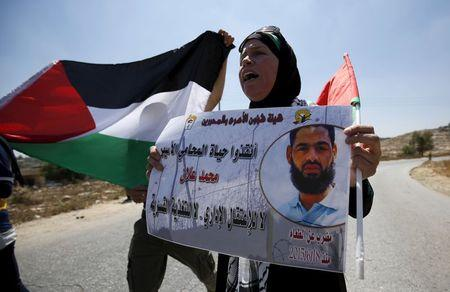 A Palestinian woman holds a picture depicting Palestinian detainee Mohammed Allan during a protest in solidarity with Allan, in the West Bank village of Nabi Saleh, near Ramallah August 14, 2015.  REUTERS/Mohamad Torokman