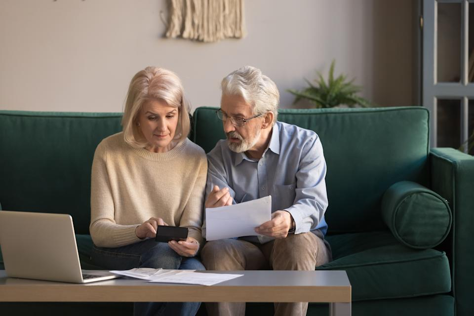 Serious mature couple calculating bills to pay, checking domestic finances, middle aged family managing, planning budget, expenses, grey haired man and woman reading bank loan documents at home