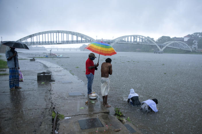 """Relatives of a person who died of reasons other than COVID-19 perform rituals in Periyar river during heavy rains in Kochi, Kerala state, India, Saturday, May 15, 2021. With cyclonic storm """"Tauktae"""" intensifying over the Arabian Sea, the southern state is receiving heavy rains amid a lockdown imposed to curb the spread of coronavirus. (AP Photo/R S Iyer)"""