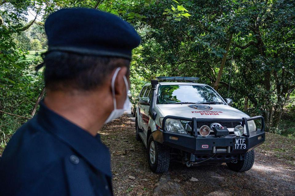 File picture shows a policeman cop standing guard as a forensic vehicle leaves the main entrance of the location where the body of Franco-Irish teenager Nora Anne Quoirin was found, near the Dusun resort, in Seremban on August 13, 2020. — AFP pic