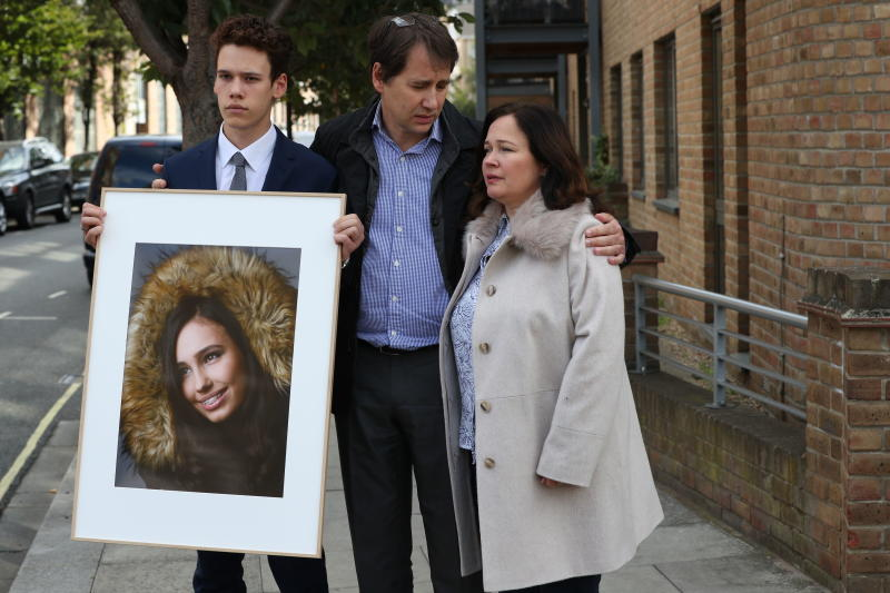 Nadim and Tanya Ednan-Laperouse, with their son Alex, prepare to speak to the media outside West London Coroners Court, Friday Sept. 28, 2018, following the inquest into the death of Natasha Ednan-Laperouse, 15, seen on poster, who died after suffering a fatal allergic reaction on a flight from London to Nice after eating a Pret A Manger sandwich at Heathrow Airport. Natasha's father, Nadim, said Friday he hoped the death of their daughter could serve as a watershed moment to make meaningful changes to allergy labelling on food packaging. (Jonathan Brady/PA via AP)