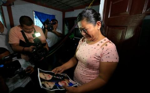 Rosa Ramirez cries at pictures of her son and granddaughter - Credit:  Antonio Valladares/ AP