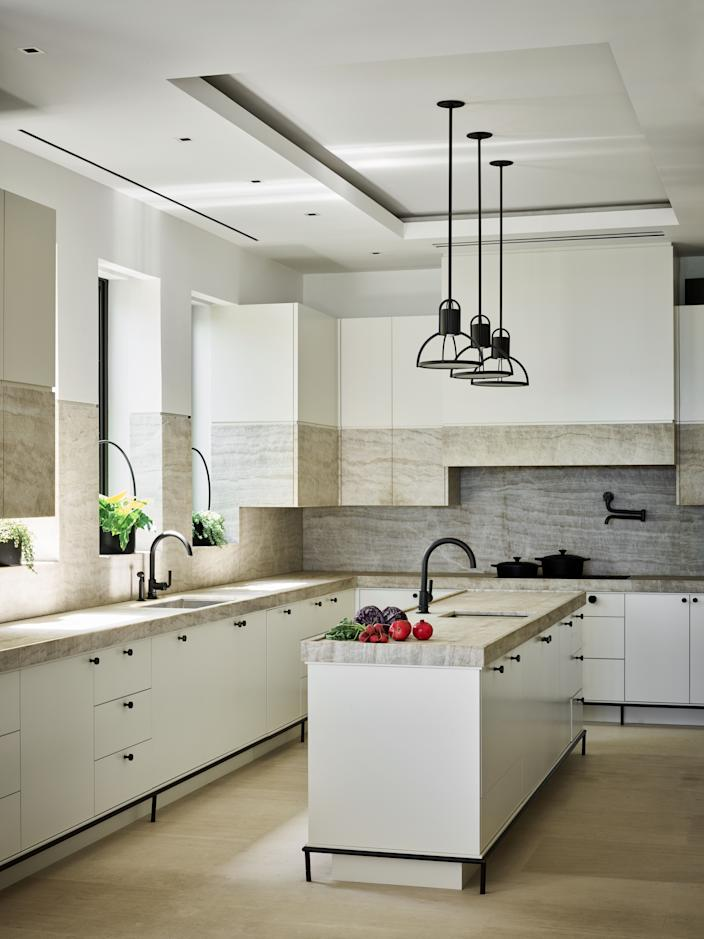 """<div class=""""caption""""> Joyner enlisted his private chef to help design his kitchen to her specifications. Weceselman drew inspiration from French designs for the overall aesthetic. The unique cabinet composition is wood with stone inserts and were custom created by Wecselman Design. The pendants over the island are by <a href=""""https://www.hollyhunt.com/"""" rel=""""nofollow noopener"""" target=""""_blank"""" data-ylk=""""slk:Holly Hunt"""" class=""""link rapid-noclick-resp"""">Holly Hunt</a>. </div>"""