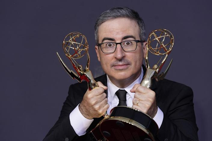 John Oliver holds an Emmy statuette in each hand.