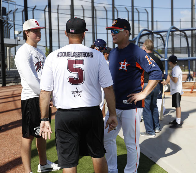 Houston Astros manager A.J. Hinch talks with Stoneman Douglas High School baseball coach Todd Fitz-Gerald, center, and his son, Hunter Fitz-Gerald, left, last month. (AP)