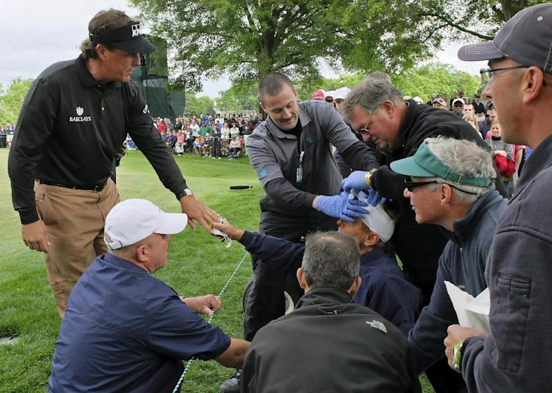 Phil Mickelson, left, consoles a fan while she is tended to after being struck in the head by Mickelson's approach shot on the 16th hole during the third round of the Wells Fargo Championship golf tournament at Quail Hollow Club in Charlotte, N.C., Saturday, May 4, 2013. (AP Photo/Chuck Burton)