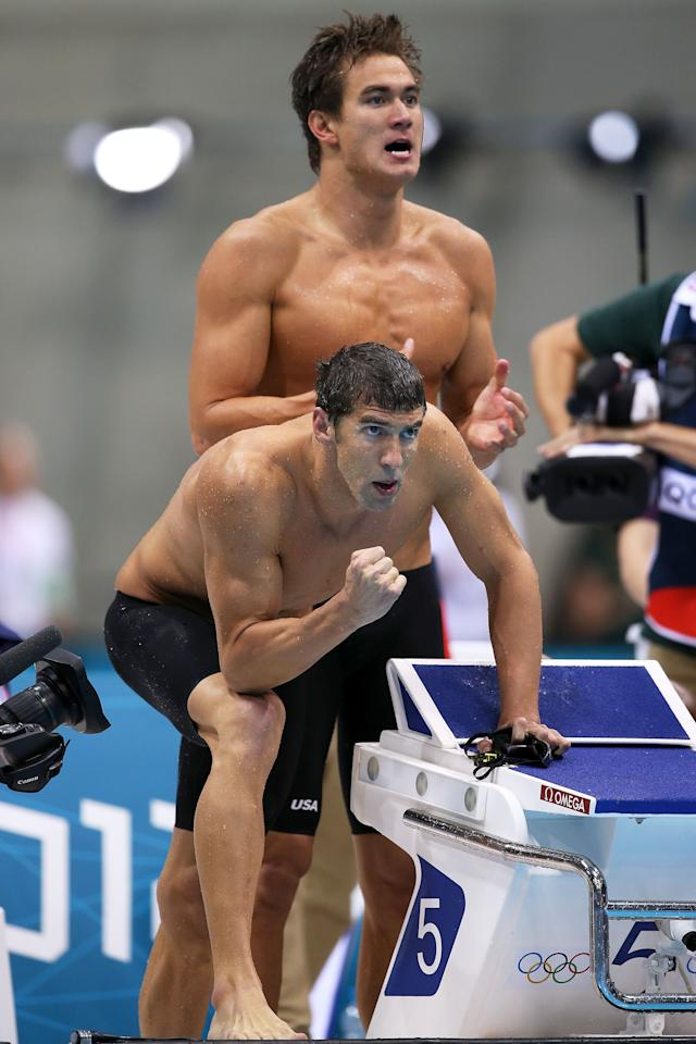 LONDON, ENGLAND - JULY 29:  Michael Phelps (Front) and Nathan Adrian of the United States cheer on their teammates during the Men's 4 x 100m Freestyle Relay final on Day 2 of the London 2012 Olympic Games at the Aquatics Centre on July 29, 2012 in London, England.  (Photo by Clive Rose/Getty Images)