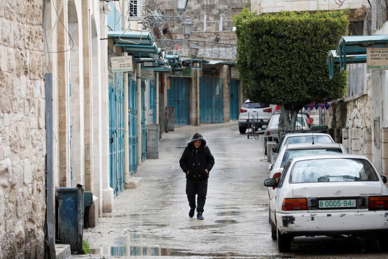 Man walks past closed shops as preventive measures are taken against the coronavirus, in Bethlehem in the Israeli-occupied West Bank