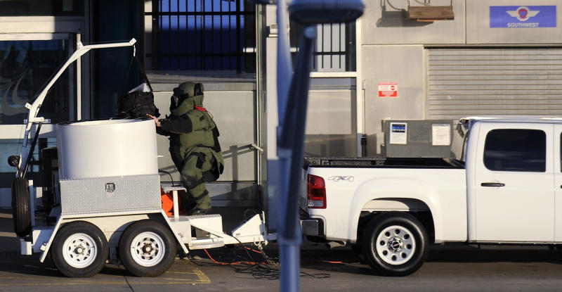 The bomb squad removes a piece of luggage at a closed down North Terminal at the Detroit Metropolitan Airport in Romulus, Mich., Monday April 1, 2013.  Authorities evacuated the smaller of two terminals at the airport for about two hours and detained one person as a bomb squad responded to a suspicious item at a security checkpoint.  (AP Photo/Detroit News, David Coates)  DETROIT FREE PRESS OUT; HUFFINGTON POST OUT