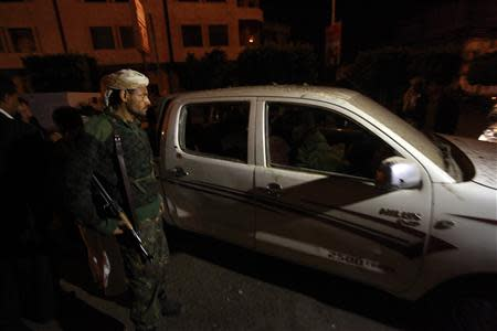 A soldier stands near a damaged car at the site of an explosion, near former President Ali Abdullah Saleh's house which is also within close proximity to the French embassy, in Sanaa February 3, 2014. REUTERS/Mohamed al-Sayaghi