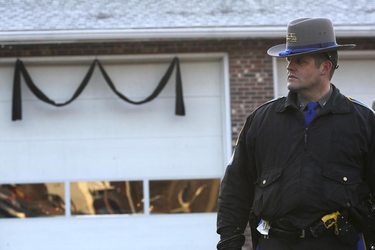 Bunting hangs on the Sandy Hook fire house as a Connecticut State Trooper stands guard outside, Saturday, Dec. 15, 2012 in Sandy Hook village of Newtown, Conn. The massacre of 26 children and adults at Sandy Hook Elementary school elicited horror and soul-searching around the world even as it raised more basic questions about why the gunman, 20-year-old Adam Lanza, would have been driven to such a crime and how he chose his victims. (AP Photo/Mary Altaffer)