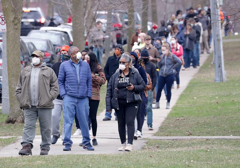 Micheal Singleton, second left, and his wife Gladys wait in line to vote continued a few blocks south of the polling location at Riverside High School in Milwaukee on Tuesday, April 7, 2020.