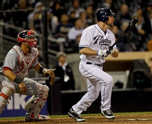 San Diego Padres pinch hitter Mark Kotsay and Washington Nationals catcher Wilson Ramos watch the flight of Kotsay's two run double in the eighth inning a baseball game won by the Padres 2-1 Thursday, April 26, 2012 in San Diego. (AP Photo/Lenny Ignelzi)