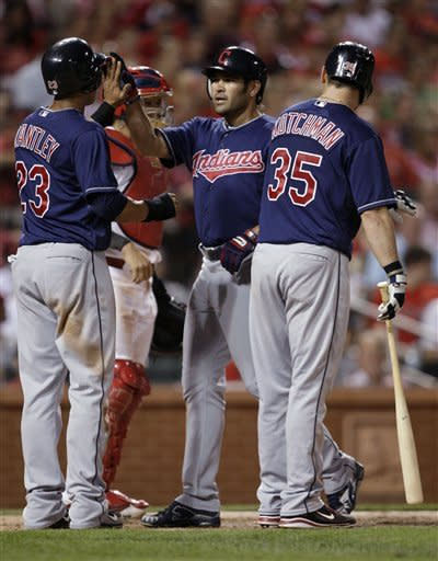 Cleveland Indians' Johnny Damon, center, celebrates with teammates Michael Brantley (23) and Casey Kotchman (35), near St. Louis Cardinals catcher Yadier Molina (4), after hitting a two-run home run in the seventh inning of a baseball game, Friday, June 8, 2012, in St. Louis.(AP Photo/Tom Gannam)