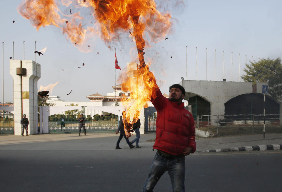 A Nepalese protester burns an effigy of prime minister Khadga Prasad Oli in front of the parliament building in Kathmandu, Nepal, Sunday, Dec. 20, 2020. Nepal's president dissolved Parliament on Sunday after the prime minister recommended the move amid an escalating feud within his Communist Party that is likely to push the Himalayan nation into a political crisis. Parliamentary elections will be held on April 30 and May 10, according to a statement from President Bidya Devi Bhandari's office. (AP Photo/Niranjan Shrestha)
