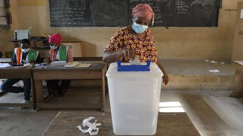A voter casts her ballot at a polling station in Abobo, a suburb in Abidjan, on October 31, 2020.