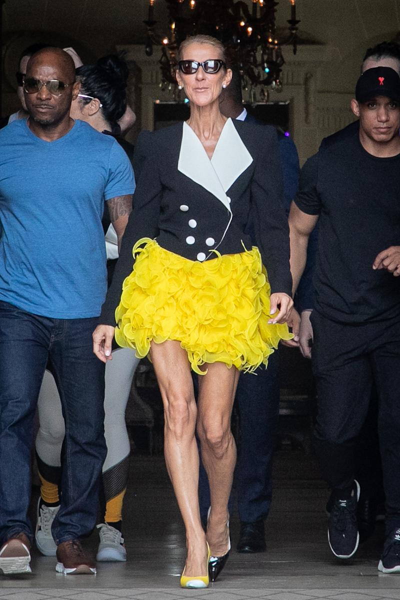 A photo of singer Céline Dion in a yellow skirt and black jacket in Paris, France.