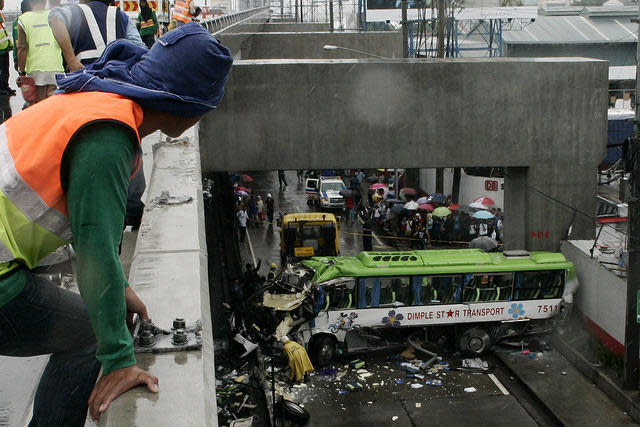 Workers try to clear the road after a passenger bus fell off from Skyway in Sucat, Paranaque City, south of Manila.