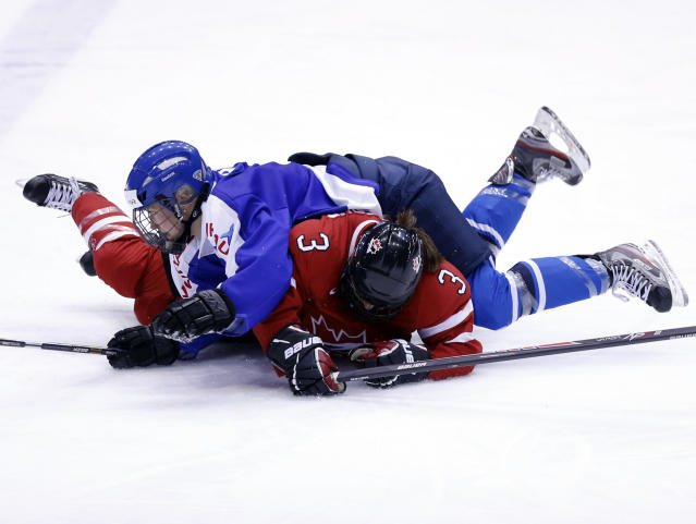 Finland's Venla Hovi (9) lands on Canada's Jocelyne Larocque (3) during the third period of a Four Nations Cup women's hockey game on Tuesday, Nov. 5, 2013, in Lake Placid, N.Y. Canada won, 3-1. (AP Photo/Mike Groll)