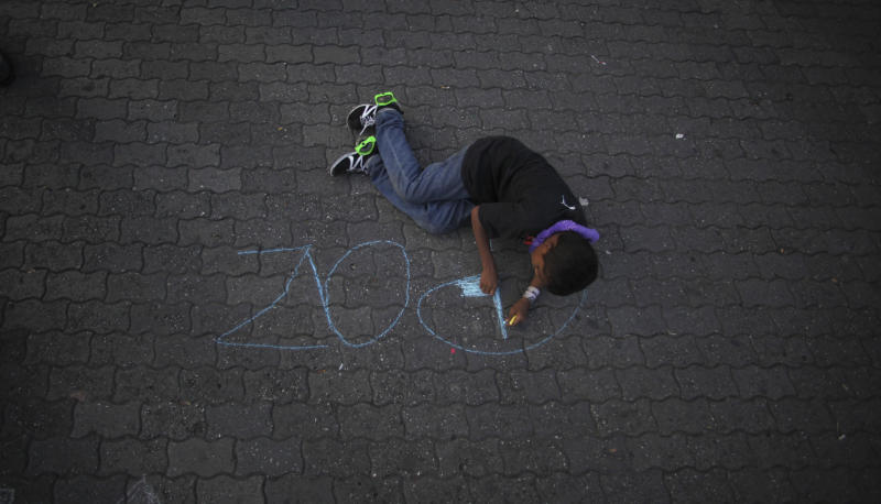 "In this photo taken Tuesday, May 22, 2012, a boy colors in the letter ""P"" with chalk after spelling the Spanish word ""Paz,"" or ""Peace,"" at an event against violence, in Caracas, Venezuela. The government says more than 14,000 people were killed in Venezuela last year, giving the country a murder rate of 50 per 100,000 people and making it one of the most violent countries in Latin America and the world. The murder rate has more than doubled since 1998, when Venezuela's President Hugo Chavez was first elected. (AP Photo/Fernando Llano)"