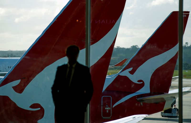 FILE PHOTO: A passenger stands in front of a window where Qantas planes are parked at Melbourne Airport, Australia
