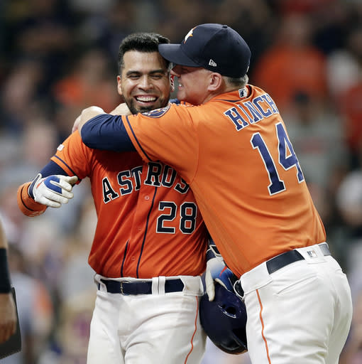 Houston Astros' Robinson Chirinos (28) is hugged by manager AJ Hinch (14) after Chirinos' double scored Yuli Gurriel to give the Astros a 4-3 win over the Baltimore Orioles in 11 innings in a baseball game Friday, June 7, 2019, in Houston. (AP Photo/Michael Wyke)