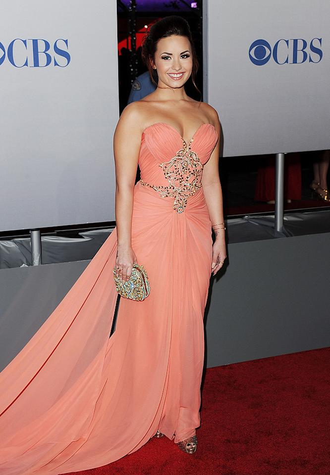 Miley's pal Demi Lovato made a dramatic entrance in a peach gown, which accentuated her curvaceous physique. (01/11/2012)