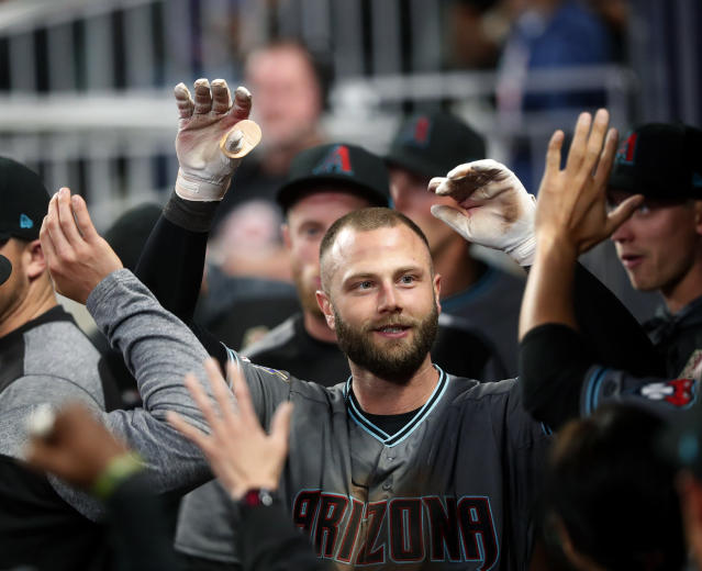 Arizona Diamondbacks' Christian Walker, left, celebrates in the dugout after hitting a solo-home run against the Atlanta Braves in the ninth inning of a baseball game, Tuesday, April 16, 2019, in Atlanta. (AP Photo/John Bazemore)