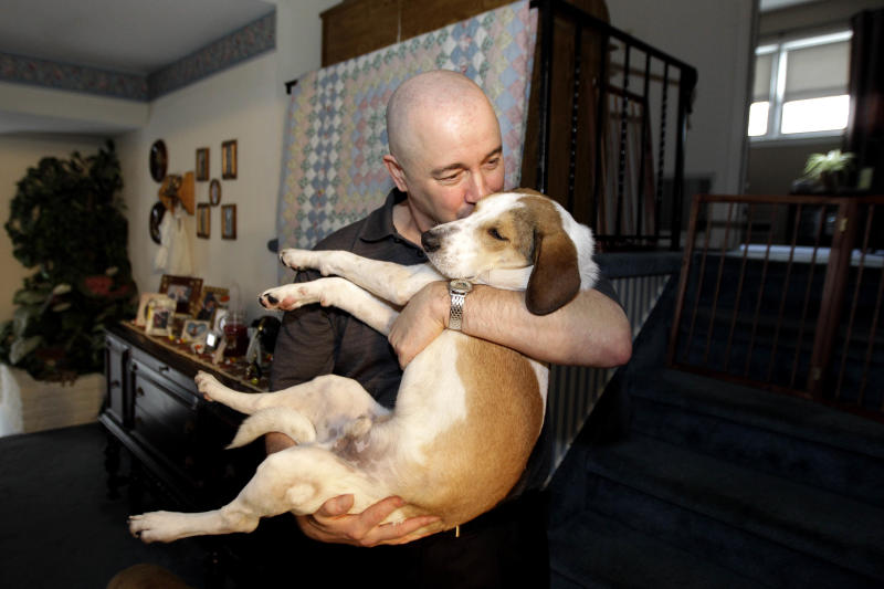 In this Nov. 16, 2011, file photo, Joe Dwyer, of Nutley, N.J., plays with his new dog Daniel, also known as the Miracle Dog. The stray beagle mix, who walked out unscathed from the carbon monoxide administered by the Animal Control Department in Florence, Ala., will be among eight shelter dogs riding on a float in the Rose Parade in Pasadena, Calif., on New Year's Day. (AP Photo/Julio Cortez, File)