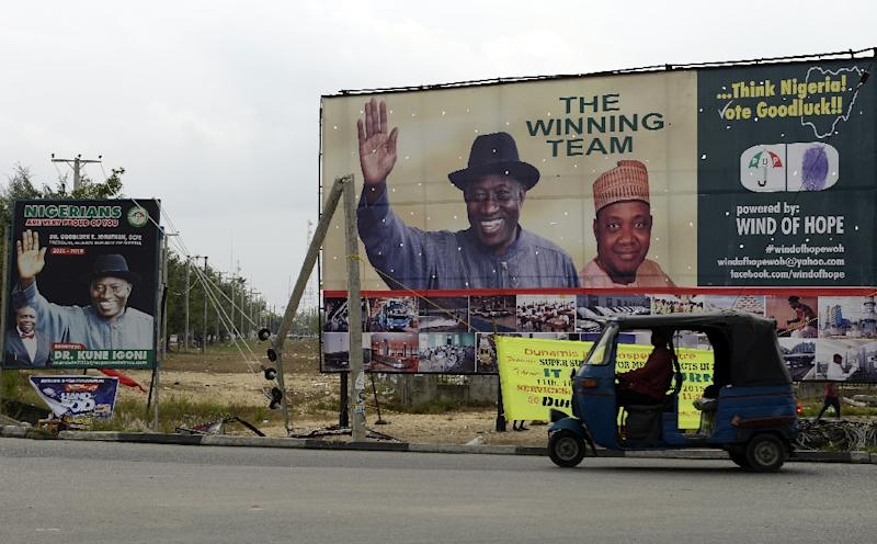 A taxi tricycle drives past campaign billboards displayed along a street in Otuoke, the home town of then Nigerian President and presidential candidate of the ruling People's Democratic Party Goodluck Jonathan in Bayelsa State, on January 27, 2015