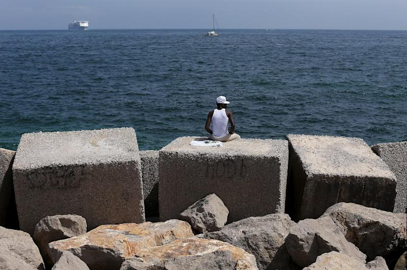 A migrant sits on a concrete block at the waterfront of the Sicilian harbour in Palermo April 19, 2015.   REUTERS/Alessandro Bianchi        TPX IMAGES OF THE DAY