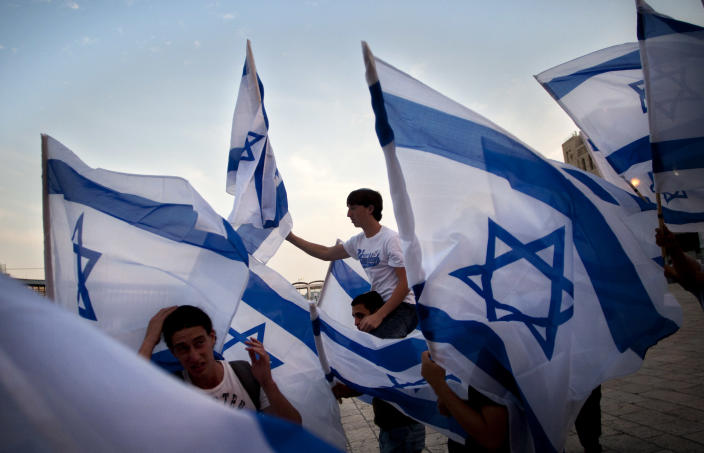 "FILE - In this Monday, May 9, 2011 file photo, Israeli youths dance with Israeli flags, prior to a prayer at the Western Wall, the holiest site where Jews can pray, marking Israel's Independence Day,in Jerusalem. The notion of Israel's ""Jewishness"" has gained both currency and controversy recently because of Prime Minister Benjamin Netanyahu's demand that the Palestinians recognize it explicitly as part of an agreement and plans by a broad-based group of Israelis to lobby the Knesset to declare the country a Jewish state by law. (AP Photo/Sebastian Scheiner, File)"