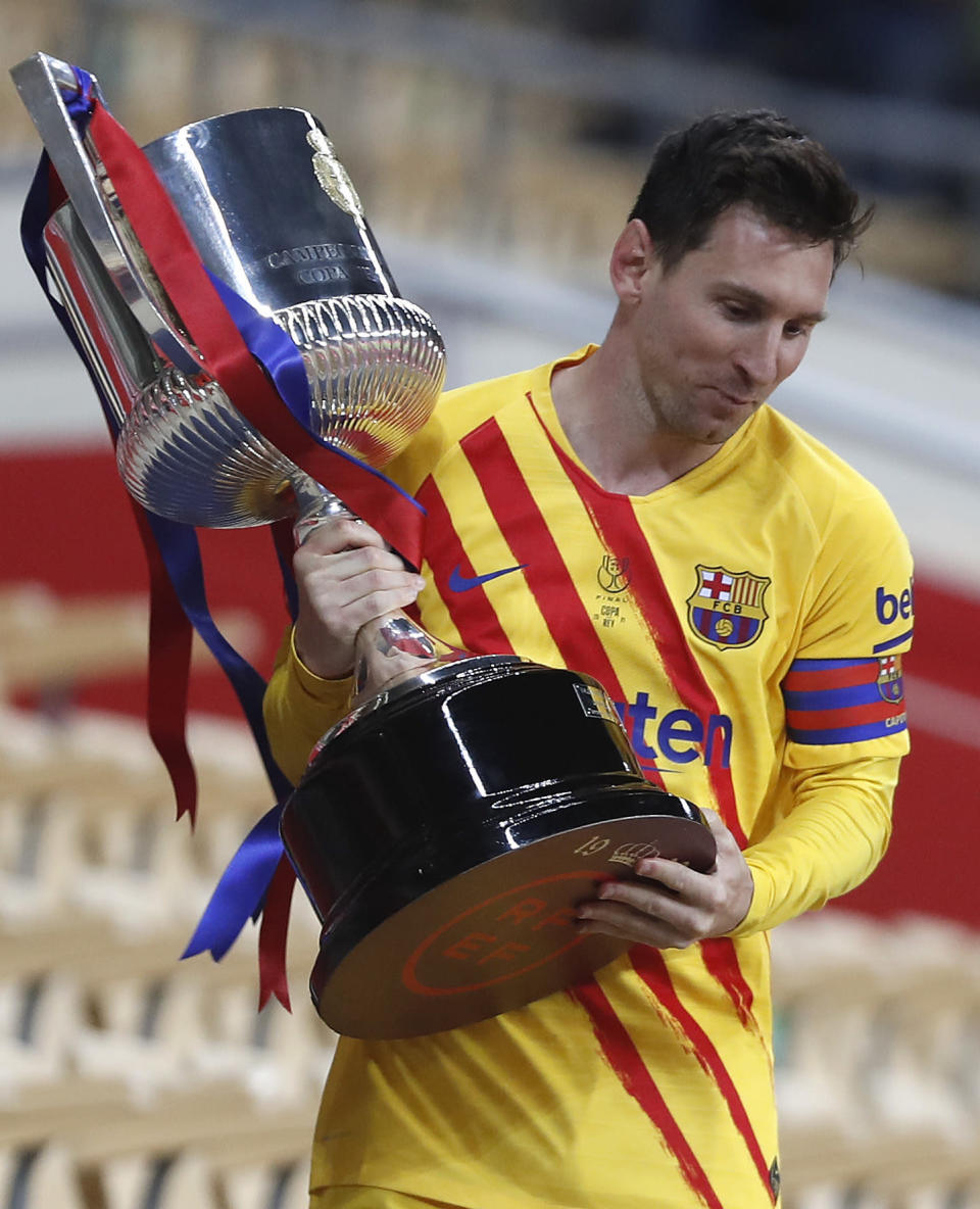 Barcelona's Lionel Messi holds the trophy after winning the Spanish Copa del Rey final 2021 against Athletic Bilbao at La Cartuja stadium in Seville, Spain, Saturday April 17, 2021. (AP Photo/Angel Fernandez)
