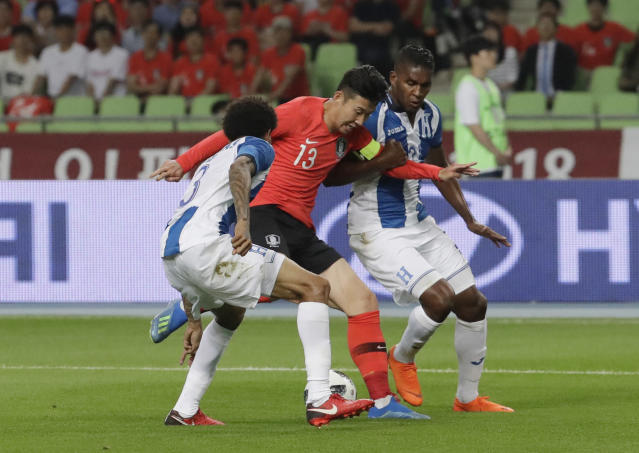 South Korea's Son Heung-min, center, fights for the ball against Honduras Henry Figueroa, left, and Brayan Beckeles during their friendly soccer match in Daegu, South Korea, Monday, May 28, 2018. (AP Photo/Lee Jin-man)