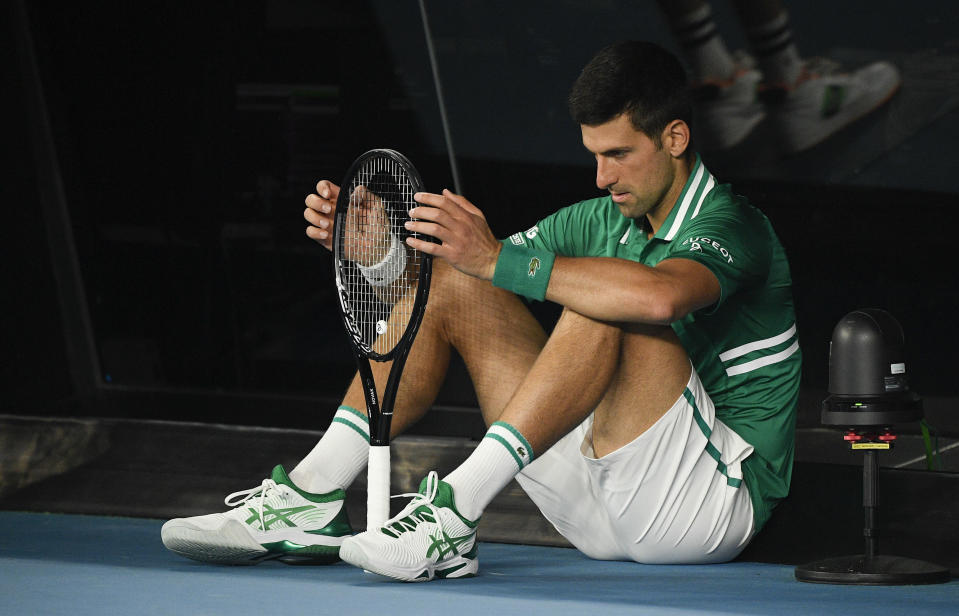 Serbia's Novak Djokovic sits down at the back of the court between games during his quarterfinal against Germany's Alexander Zverev at the Australian Open tennis championship in Melbourne, Australia, Tuesday, Feb. 16, 2021.(AP Photo/Andy Brownbill)