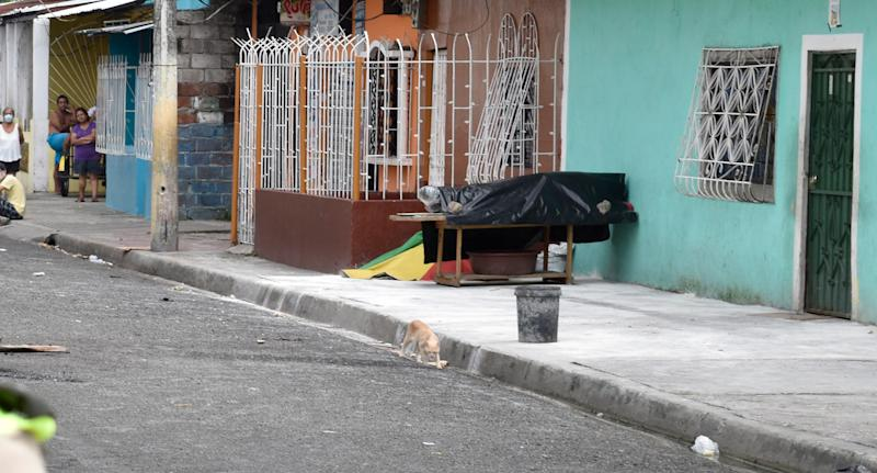 Black plastic covers a person's body outside a Guayaquil home.